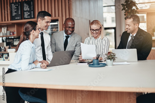 Obraz Smiling group of diverse businesspeople working around an office - fototapety do salonu