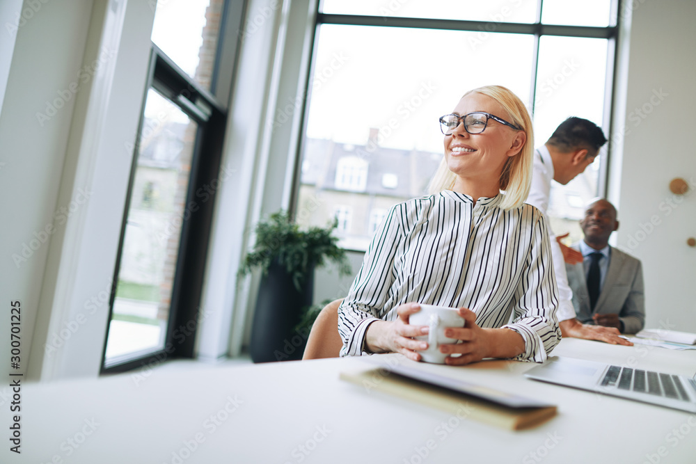 Fototapety, obrazy: Smiling businesswoman enjoying a coffee during her office break