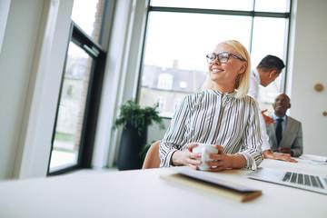 Fototapeta na wymiar Smiling businesswoman enjoying a coffee during her office break