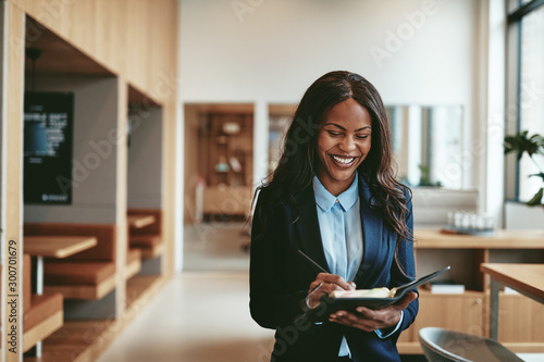 Laughing African American businesswoman walking in in office wri