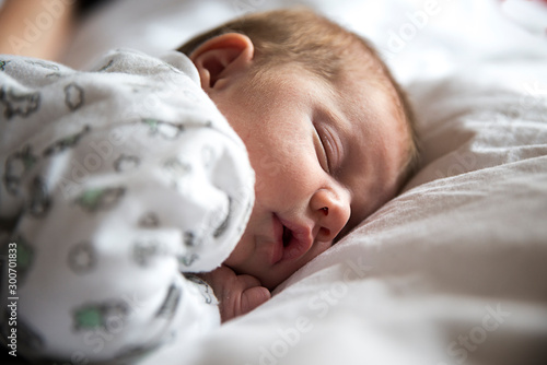 adorable bebé durmiendo en la cama entre sábanas blancas Canvas Print