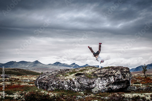 Canvas Print Man doing handstand in mountain scenery.