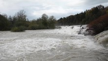 Left Pan View Of Raging Dirty River Flooding Over A Dam With Washed Up Tree