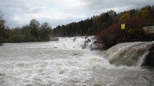 Static View Of Raging Dirty River Flooding Over A Dam With Washed Up Tree And A Canal