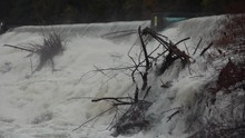 Static Close Up View Of Raging Dirty River Flooding Over A Dam With Washed Up Tree
