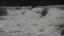 Static Close Up View Of Dirty River Flooding Over Small Dam