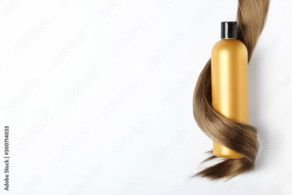 Fototapeta Shampoo bottle wrapped in lock of hair isolated on white, top view. Natural cosmetic products