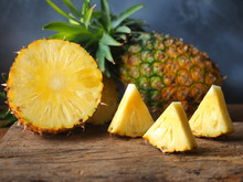 Ripe Pineapple Fruit Cut In Half And Triangle Shape On A Rustic Wooden Table For High Fiber Fruits Concept.
