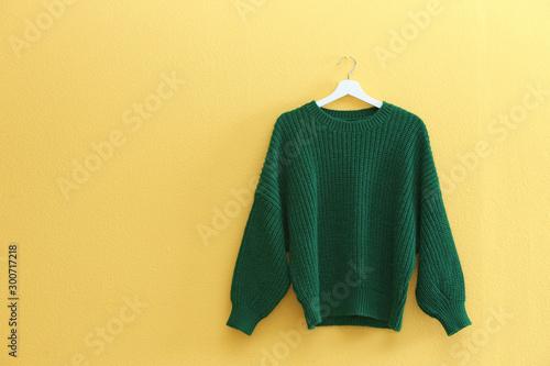 Obraz Hanger with stylish sweater on yellow wall - fototapety do salonu