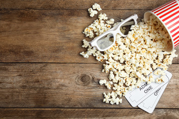 Popcorn, cinema tickets and 3d glasses  on wooden background, flat lay. Space...