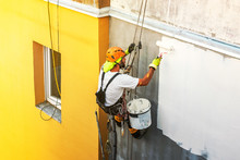 Industrial Rope Access Worker Hanging From The Building While Painting The Exterior Facade Wall. Industrial Alpinism Concept Image. Top View
