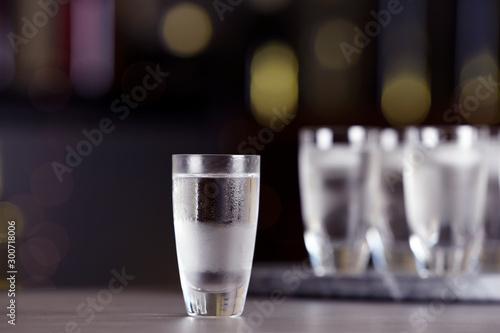 Shot of vodka on table against blurred background Fototapeta
