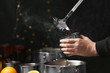 canvas print picture - Woman pouring hot mulled wine into mug against blurred background, closeup