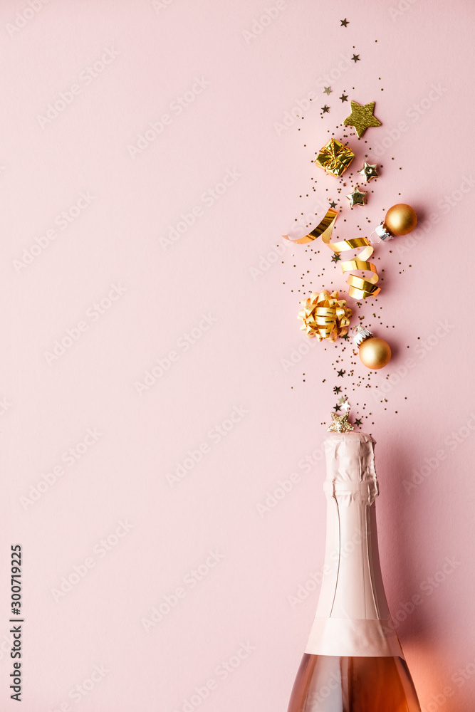 Fototapeta Flat lay of Celebration. Champagne bottle and golden decoration on pink background