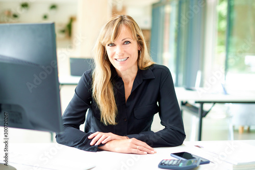 Fotografía  Portrai tof middle aged businesswoman sitting at office desk while looking at ca