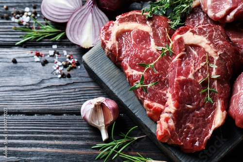 Fotografiet Fresh raw meat steaks on black wooden table, flat lay