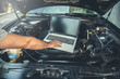 man to repair car with hand computer