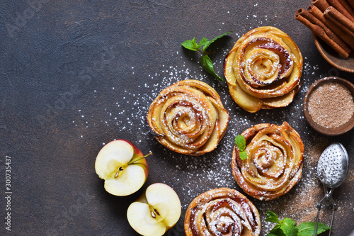 Photo Dish of apple roses baked in puff pastry on a dark concrete background with apples
