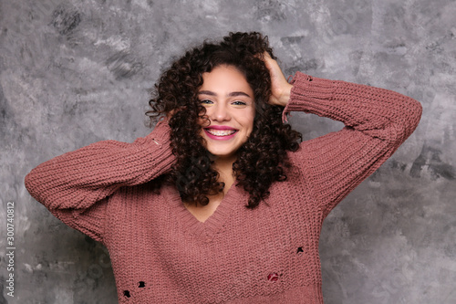 Fotografía Portrait of happy beautiful woman with long bouncy curles hairstyle and professional make up on, posing over grunged stone background