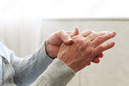 Elderly woman applying moisturizing lotion cream on hand palm, easing aches Canvas Print