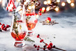 canvas print picture - Winter alcoholic cocktail with red berries, liquor, gin, thyme and vodka for Christmas or New Year. Holiday table setting