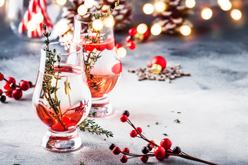 Winter alcoholic cocktail with red berries, liquor, gin, thyme and vodka for Christmas or New Year. Holiday table setting