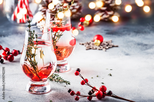 Poster Pays d Europe Winter alcoholic cocktail with red berries, liquor, gin, thyme and vodka for Christmas or New Year. Holiday table setting