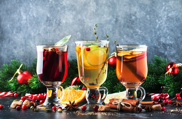 Mulled wine and mulled cider. Hot winter drinks and cocktails for christmas or new year's eve in glass mugs with spices and citrus fruit