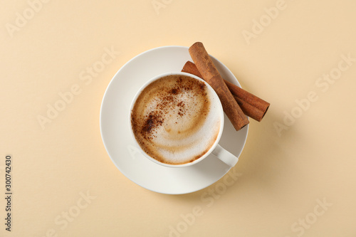 Canvas Prints Cafe Cappuccino with cinnamon on beige background, space for text