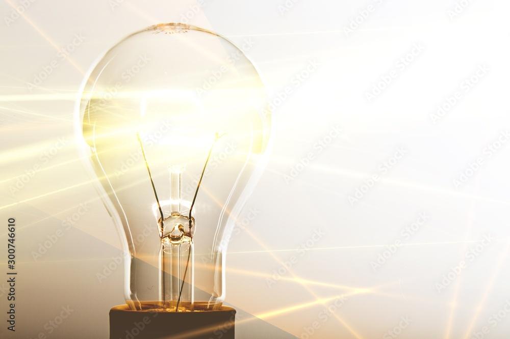 Fototapeta Glowing glass light bulb on background