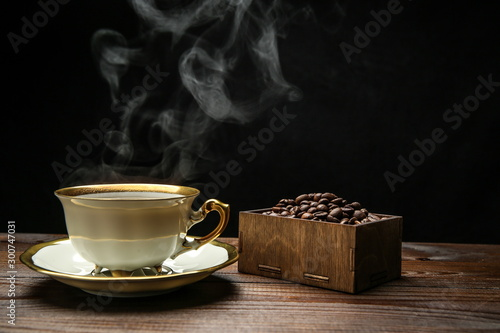 Wall Murals Cafe cup of hot coffee on a wooden surface on a black background. background with roasted coffee grains. steam from a cup of coffee