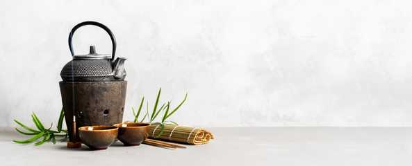 Simple still life with tea set, scattered tea, bamboo Mat, sticks, incense. Asian background with space for text.