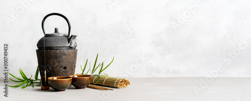 Foto auf Leinwand Tee Simple still life with tea set, scattered tea, bamboo Mat, sticks, incense. Asian background with space for text.