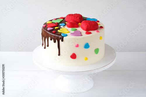 White cake decorated with colorful hearts, confectionery sprinkles and drenched in chocolate on a white background Canvas Print