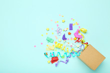 Colorful Ribbons With Stars, Confetti And Paper Bag On Blue Background