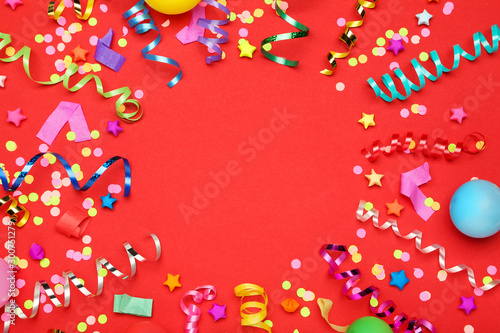 Obraz Colorful ribbons with paper stars and confetti on red background - fototapety do salonu