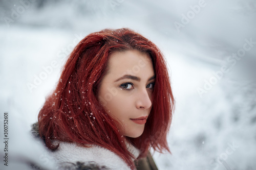 Canvas Print Beautiful woman with dyed red hair outdoors surrounded by snow