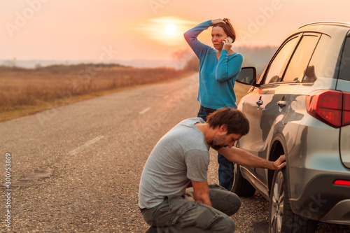 Fotobehang Hoogte schaal Couple repairing car flat tire on the road