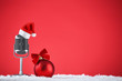 Retro microphone with santa hat and bauble on red background