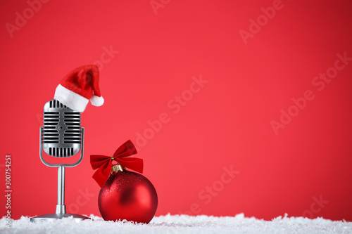 Retro microphone with santa hat and bauble on red background Obraz na płótnie