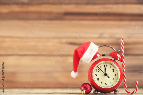 Stampa su Tela  Red alarm clock with santa hat, candy and bauble on brown wooden background