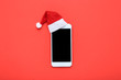canvas print picture - Santa hat with smartphone on red background