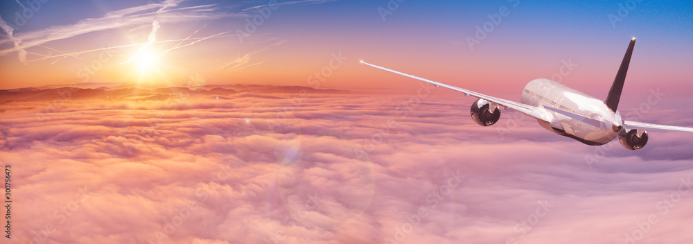 Fototapety, obrazy: Commercial airplane flying above dramatic clouds during sunset.