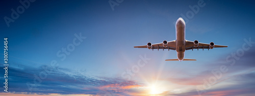 Commercial airplane flying above dramatic clouds during sunset. Fotobehang