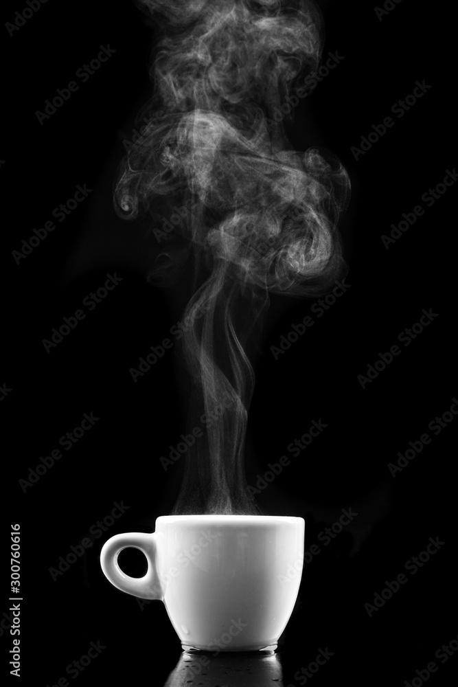 Fototapeta A white mug of warm drink and steam. Tasty hot coffee on a dark table.