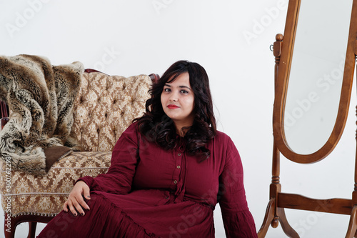 Cuadros en Lienzo Attractive south asian woman in deep red gown dress posed at studio on white background against mirror and chair
