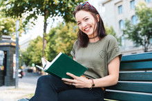 Portrait Of Smiling Young Woman Sitting On Bench With A Book