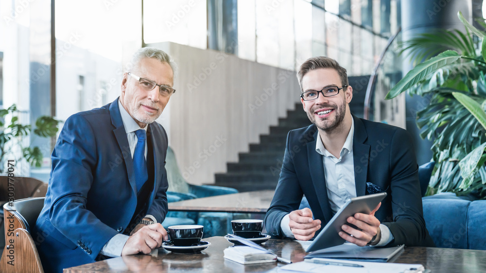 Fototapety, obrazy: Portrait of two successful businessmen working and sitting on sofa in office lobby