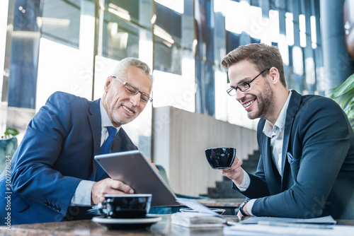 Obraz Senior businessman using digital tablet and discuss information with young man in suit on a meeting - fototapety do salonu