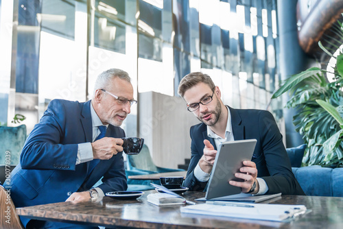 Fototapeta Mature boss and young business man working together using digital tablet in office hall obraz